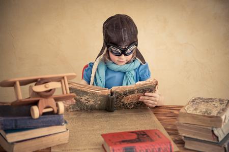 niños leyendo: Niño se hace pasar por un piloto. Niño jugando en casa. Los viajes, la libertad y el concepto de la imaginación Foto de archivo