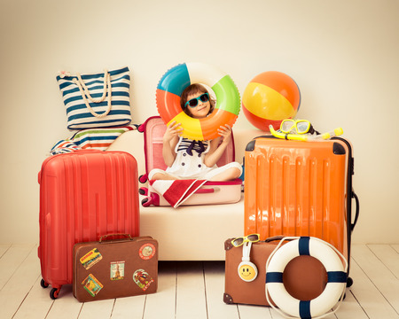 suitcases: Happy child ready for a summer vacation. Kid having fun at home