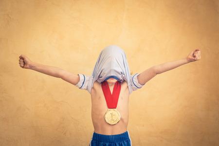 triunfador: Niño está fingiendo ser un jugador de fútbol. el concepto de éxito y ganador