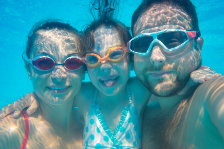 Family having fun in swimming pool. Underwater funny portrait. Summer vacation Reklamní fotografie - 54979890