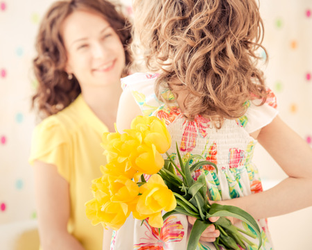 Woman and child with bouquet of flowers at home. Spring family holiday concept. Mothers day Stock Photo