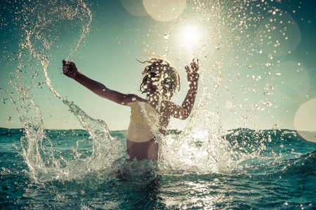 Happy child playing in the sea. Kid having fun outdoors. Summer vacation and healthy lifestyle concept. Toned image Stock Photo