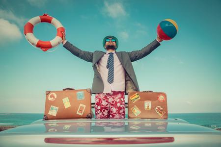 Erfolgreiche junge Geschäftsmann auf einem Strand. Man stand im Cabrio Oldtimer. Sommerferien und Freiheit Reise-Konzept. getöntes Bild