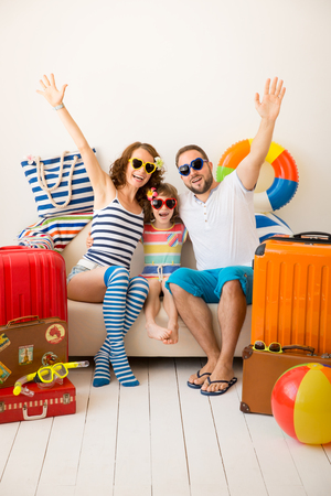 Happy family ready for a summer vacation. Father, mother and child having fun at home