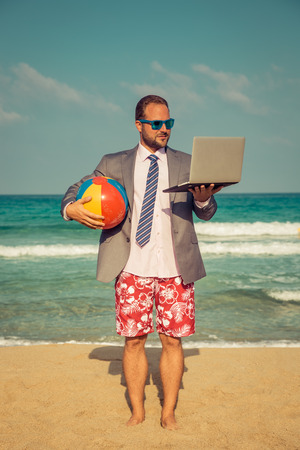 Portrait of funny businessman on the beach. Man having fun by the sea. Summer vacation and travel concept Standard-Bild