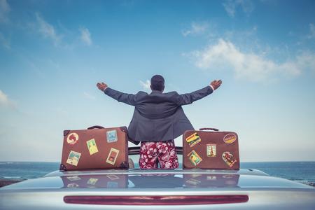 uomo felice: Giovane imprenditore di successo su una spiaggia. L'uomo in piedi in auto cabriolet classica. Vacanze estive e concetto di viaggio Archivio Fotografico