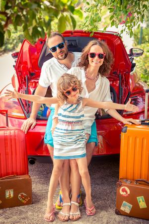 Gelukkige familie klaar om te struikelen. Mensen die zich dichtbij rode auto. Zomer vakantie en reizen concept