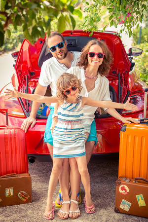 Happy family ready to trip. People standing near red car. Summer vacation and travel concept