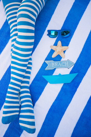 Slim woman legs on a beach. Summer vacation and travel concept. Top view