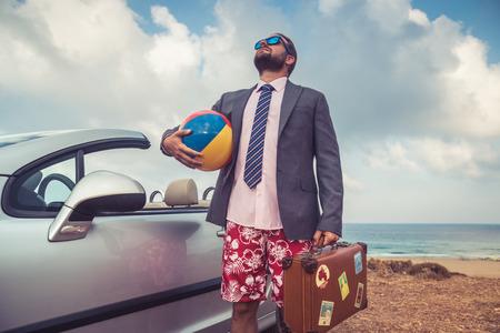 joven hombre de negocios con éxito en una playa. El hombre de pie cerca del coche descapotable clásico. Las vacaciones de verano y el concepto de viaje