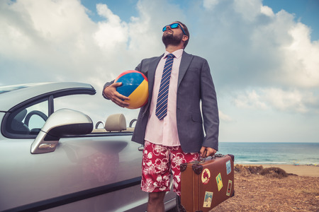 vacation: Successful young businessman on a beach. Man standing near cabriolet classic car. Summer vacations and travel concept