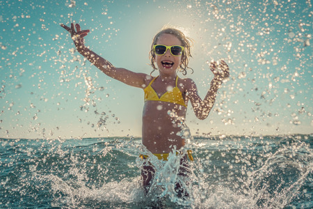 playing in the sea: Happy child playing in the sea. Kid having fun outdoors. Summer vacation and healthy lifestyle concept. Toned image Stock Photo