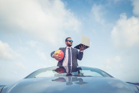 dream car: joven hombre de negocios con éxito en una playa. El hombre de pie en el coche descapotable clásico. Las vacaciones de verano y el concepto de viaje