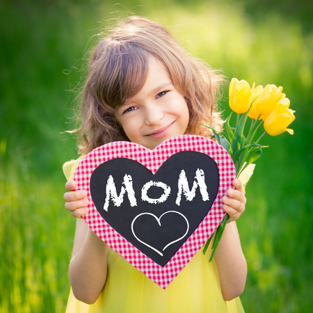 mother: Child holding card blank and bouquet of flowers against green background. Spring family holiday concept. Mothers day