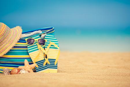Flip-flops en zak op zandig strand tegen blauwe zee en lucht achtergrond. Zomervakantie concept