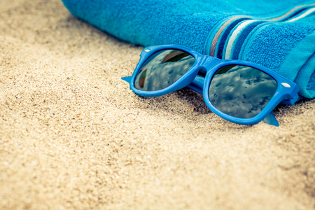 Towel and sunglasses on sandy beach against blue sea and sky background. Summer vacation concept