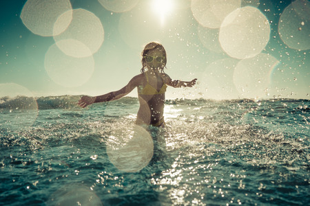 swimming silhouette: Blurred motion silhouette of happy child playing in the sea. Kid having fun outdoors. Summer vacation and healthy lifestyle concept. Toned image