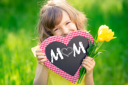 Child holding card blank and bouquet of flowers against green background. Spring family holiday concept. Mothers day