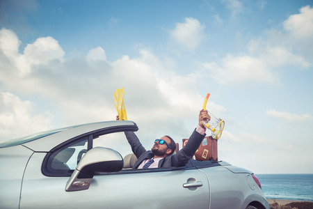 Successful young businessman on a beach. Man sitting in the cabriolet classic car. Summer vacations and travel concept