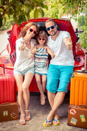 행복한 가족 여행 준비. 빨간 차 근처에 서있는 사람들. 여름 휴가 및 여행 개념