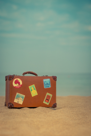 vintage background: Vintage suitcase on sandy beach against blue sea and sky background. Summer vacation and travel concept