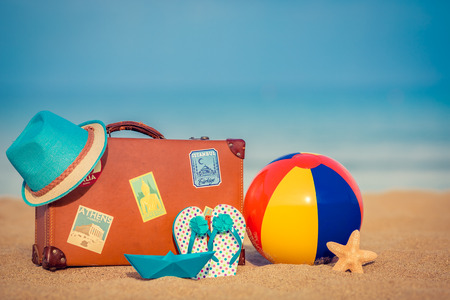 item: Vintage suitcase and flip-flops on sandy beach against blue sea and sky background. Summer vacation concept