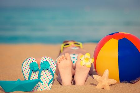 说谎在沙滩的孩子在蓝色海附近。暑假和健康的生活方式概念
