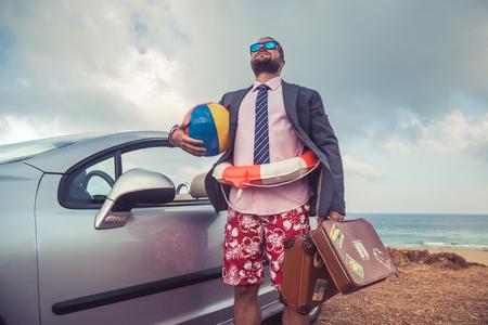 Succès jeune homme d'affaires sur une plage. Homme debout près de la voiture cabriolet classique. Les vacances d'été et le concept de Voyage