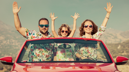 Gelukkig gezin reizen per auto in de bergen. Mensen die pret in rode cabriolet. Zomervakantie concept