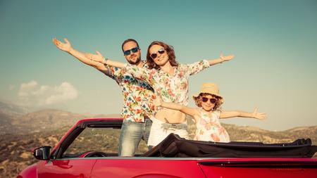Gelukkig gezin reizen per auto in de bergen. Mensen die pret in rode cabriolet. Zomervakantie concept Stockfoto