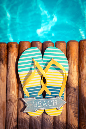 Flip-flops on wood against blue water background. Summer vacation concept Banco de Imagens