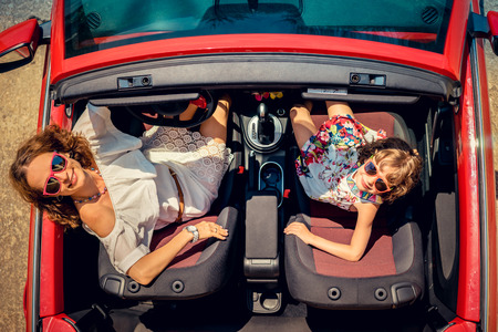 Happy family travel by car. Woman and child having fun in red cabriolet. Summer vacation and travel concept. Top view