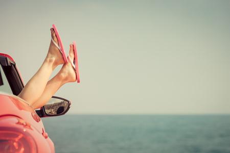 Młoda kobieta relaksu na plaży. Dziewczynka zabawy w czerwonym kabriolet przeciwko t? A stonowanych niebo. Letnie wakacje i koncepcji podróży Zdjęcie Seryjne