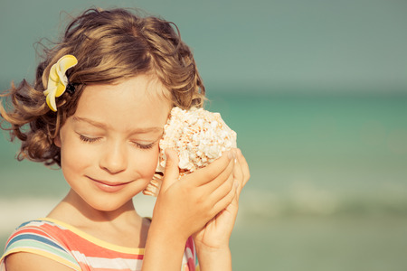 Child relaxing on the beach against sea and sky background. Summer vacation and travel concept Stock Photo