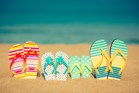 flipflops: Flip-flops on sandy beach against blue sea and sky background. Summer vacation concept