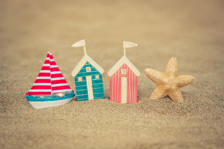 coloured: Toy house on sandy beach against blue sea and sky background. Summer vacation concept