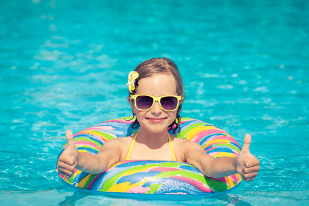 Funny portrait of child. Kid having fun in swimming pool outdoors. Summer vacation and healthy lifestyle concept Archivio Fotografico