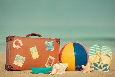 빈티지 가방 및 푸른 바다와 하늘 배경에 모래 해변에서 슬리퍼. 여름 휴가 개념 스톡 콘텐츠