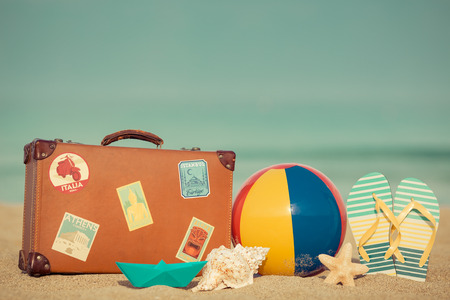 Vintage suitcase and flip-flops on sandy beach against blue sea and sky background. Summer vacation concept