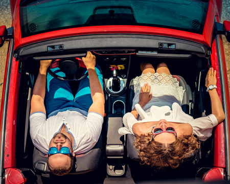 view woman: Happy couple travel by car. Woman and man having fun in red cabriolet. Summer vacation and travel concept. Top view Stock Photo