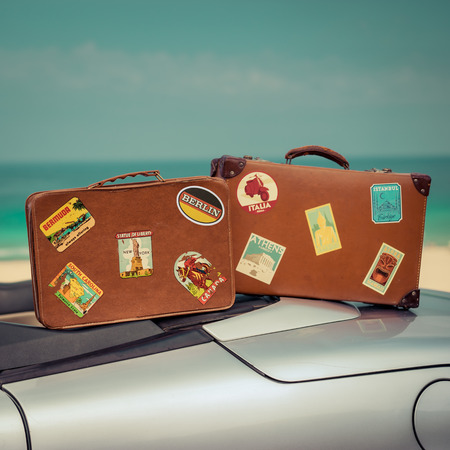 summer holidays: Vintage suitcases on cabriolet car. Summer vacation and travel concept