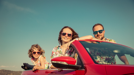 Happy family travel by car in the mountains. People having fun in red cabriolet. Summer vacation concept Standard-Bild