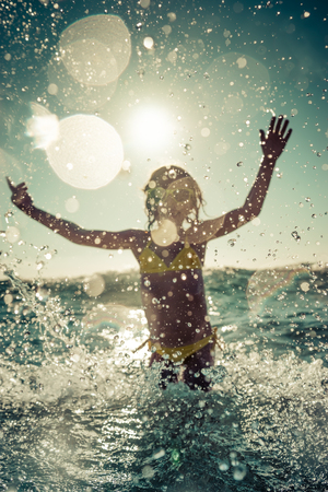 Blurred motion silhouette of happy child playing in the sea. Kid having fun outdoors. Summer vacation and healthy lifestyle concept. Toned image