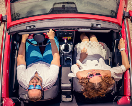 cabrio: Happy couple travel by car. Woman and man having fun in red cabriolet. Summer vacation and travel concept. Top view Stock Photo