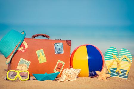 Maleta y flip-flops de la vendimia en la playa arenosa contra fondo azul del mar y del cielo. Concepto de vacaciones de verano