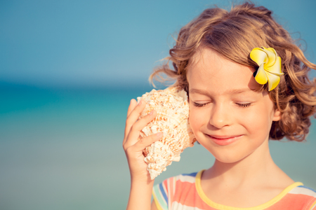 Kind am Strand entspannen gegen Meer und Himmel im Hintergrund. Sommer-Urlaub und Reise-Konzept