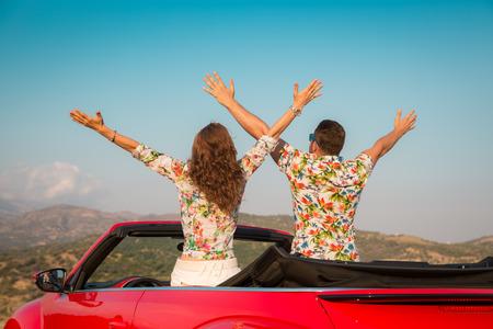 uomo rosso: Coppia felice viaggio in auto tra le montagne. La gente che si diverte in cabriolet rosso. concetto di vacanza estiva