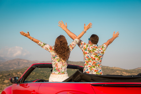 carefree: Happy couple travel by car in the mountains. People having fun in red cabriolet. Summer vacation concept