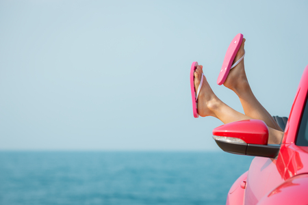 sexy woman car: Young woman relaxing on the beach. Girl having fun in red cabriolet against blue sky background. Summer vacation and travel concept