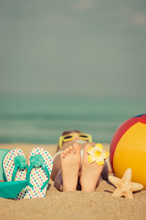 feet in sand: Child lying on sandy beach near blue sea. Summer vacation and healthy lifestyle concept